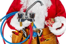 Santa Claus holding a faucet and plumbing tools